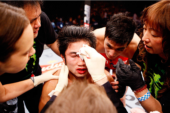 SINGAPORE - JANUARY 04:  Shunichi Shimizu is looked over after his loss to Kang Kyung Ho in their bantamweight bout during the UFC Fight Night event at the Marina Bay Sands Resort on January 4, 2014 in Singapore. (Photo by Mitch Viquez/Zuffa LLC/Zuffa LLC via Getty Images)