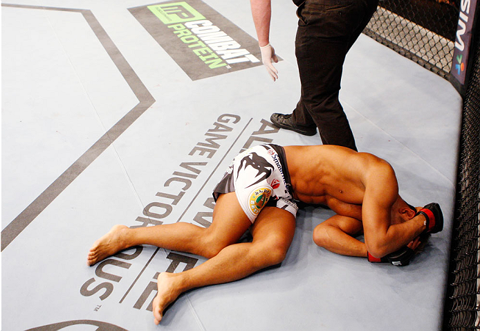SINGAPORE - JANUARY 04:  Kiichi Kunimoto lies on the ground after illegal elbows to the back of the head from his opponent, Luiz Dutra, in their welterweight bout during the UFC Fight Night event at the Marina Bay Sands Resort on January 4, 2014 in Singapore. (Photo by Mitch Viquez/Zuffa LLC/Zuffa LLC via Getty Images)
