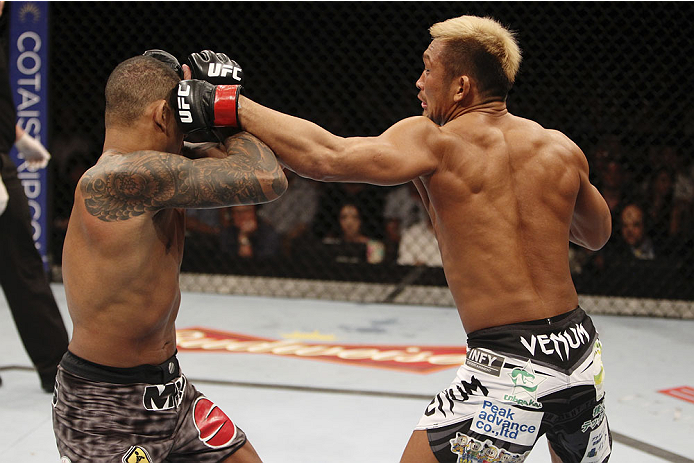 SINGAPORE - JANUARY 04: Kiichi Kunimoto goes for a punch on Luiz Dutra in their welterweight bout during the UFC Fight Night event at the Marina Bay Sands Resort on January 4, 2014 in Singapore. (Photo by Mitch Viquez/Zuffa LLC/Zuffa LLC via Getty Images)