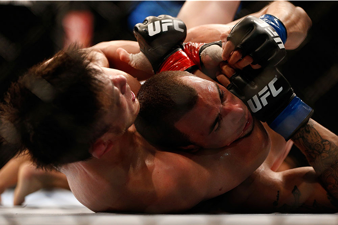SINGAPORE - JANUARY 04:  (L-R) Tatsuya Kawajiri secures a rear choke submission against Sean Soriano in their featherweight bout during the UFC Fight Night event at the Marina Bay Sands Resort on January 4, 2014 in Singapore. (Photo by Josh Hedges/Zuffa LLC/Zuffa LLC via Getty Images)