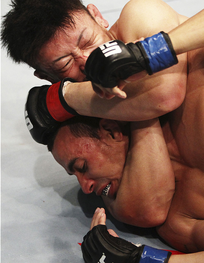 SINGAPORE - JANUARY 04:   Tatsuya Kawajiri  goes for a submission attempt on Sean Soriano in their featherweight bout during the UFC Fight Night event at the Marina Bay Sands Resort on January 4, 2014 in Singapore. (Photo by Mitch Viquez/Zuffa LLC/Zuffa LLC via Getty Images)