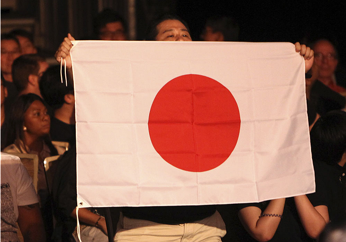 SINGAPORE - JANUARY 04:  A fan holds a Japanese flag during Katsunori Kikuno and Quinn Mulhern's during their lightweight bout during the UFC Fight Night event at the Marina Bay Sands Resort on January 4, 2014 in Singapore. (Photo by Mitch Viquez/Zuffa LLC/Zuffa LLC via Getty Images)