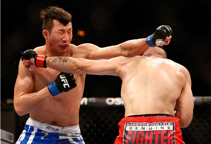 SINGAPORE - JANUARY 04:  (R-L) Tarec Saffiedine and Lim Hyun Gyu trade punches in their welterweight bout during the UFC Fight Night event at the Marina Bay Sands Resort on January 4, 2014 in Singapore. (Photo by Josh Hedges/Zuffa LLC/Zuffa LLC via Getty Images)