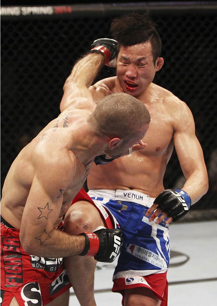 SINGAPORE - JANUARY 04:  Tarec Saffiedine lands a shot on Lim Hyun Gyu  in their welterweight bout during the UFC Fight Night event at the Marina Bay Sands Resort on January 4, 2014 in Singapore. (Photo by Mitch Viquez/Zuffa LLC/Zuffa LLC via Getty Images)