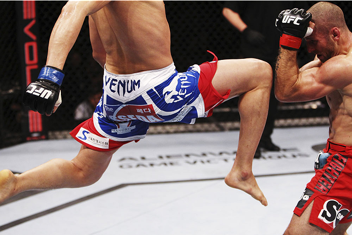 SINGAPORE - JANUARY 04:  Lim Hyun Gyu goes for a flying knee on Tarec Saffiedine in their welterweight bout during the UFC Fight Night event at the Marina Bay Sands Resort on January 4, 2014 in Singapore. (Photo by Mitch Viquez/Zuffa LLC/Zuffa LLC via Getty Images)