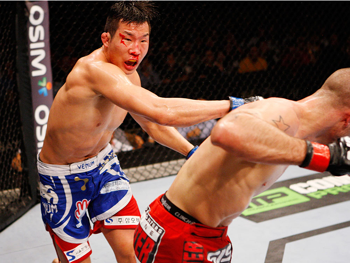 SINGAPORE - JANUARY 04:  Lim Hyun Gyu throws a punch at Tarec Saffiedine in their welterweight bout during the UFC Fight Night event at the Marina Bay Sands Resort on January 4, 2014 in Singapore. (Photo by Mitch Viquez/Zuffa LLC/Zuffa LLC via Getty Images)