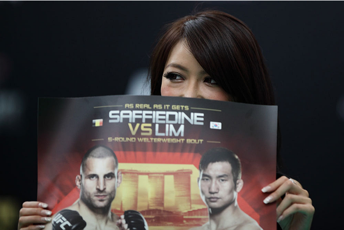 SINGAPORE - JANUARY 01:  Octagon ring girl and former Miss Japan Universe finalist, Azusa Nishigaki holds up the UFC fight night poster during the UFC Fight Night Singapore Open Workouts at the Skating Rink at The Shoppes at Marina Bay Sand on January 1, 2014 in Singapore.  (Photo by Suhaimi Abdullah/Zuffa LLC via Getty Images)