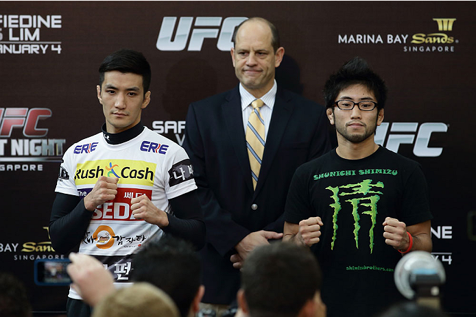 SINGAPORE - JANUARY 02:  Kyung Ho Kang (L) and Shunichi Shimizu (R) pose for a photo as Mark Fischer (C), managing director of UFC Asia, looks on during the UFC Fight Night Singapore Ultimate Media Day at the Skating Rink at The Shoppes at Marina Bay Sand on January 2, 2014 in Singapore.  (Photo by Suhaimi Abdullah/Zuffa LLC)