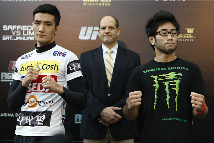 SINGAPORE - JANUARY 02:  (L-R) Opponents Kyung Ho Kang and Shunichi Shimitzu pose for photos during the UFC Fight Night Singapore Ultimate Media Day at the Shoppes at Marina Bay Sands on January 2, 2014 in Singapore. (Photo by Mitch Viquez/Zuffa LLC/Zuffa LLC via Getty Images)