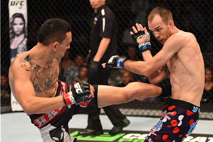 BROOMFIELD, CO - FEBRUARY 14:  (L-R) Max Holloway kicks Cole Miller in their featherweight fight during the UFC Fight Night event inside 1stBank Center on February 14, 2015 in Broomfield, Colorado. (Photo by Josh Hedges/Zuffa LLC/Zuffa LLC via Getty Images)