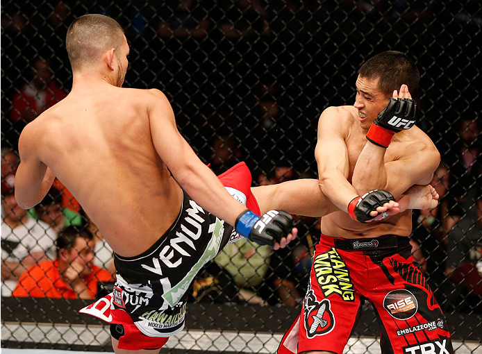 CINCINNATI, OH - MAY 10:  (L-R) Louis Smolka kicks Chris Cariaso in their flyweight fight during the UFC Fight Night event at the U.S. Bank Arena on May 10, 2014 in Cincinnati, Ohio. (Photo by Josh Hedges/Zuffa LLC/Zuffa LLC via Getty Images)