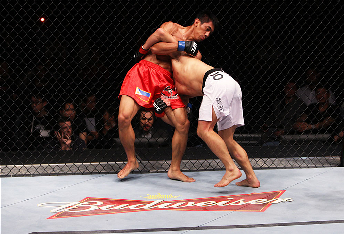 MACAU - MARCH 01:  [Mark Eddiva, left, defends a takedown from Jumabieke Tuerxun in their featherweight fight during the UFC Fight Night event at the Venetian Macau on March 1, 2014 in Macau. (Photo by Mitch Viquez/Zuffa LLC/Zuffa LLC via Getty Images)
