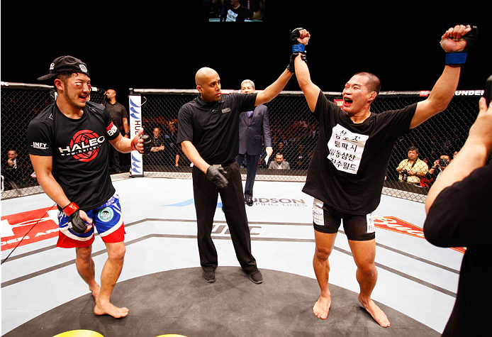 MACAU - MARCH 01:  (L to R) Yui Chul Nam smiles as Kazuki Tokudome  celebrates after hearing he was the  winner of their lightweight fight during the UFC Fight Night event at the Venetian Macau on March 1, 2014 in Macau. (Photo by Mitch Viquez/Zuffa LLC/Zuffa LLC via Getty Images)