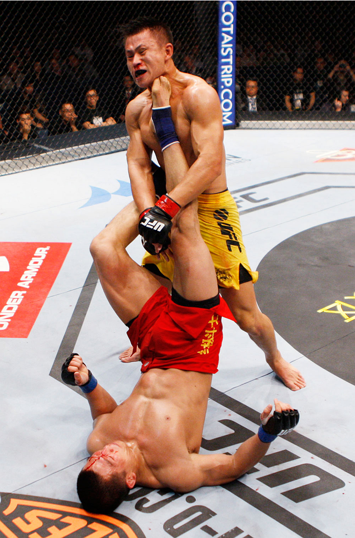 MACAU - MARCH 01:  Zhang Lipeng  gives Wang Sai an upward kick in their TUF China welterweight finals fight during the UFC Fight Night event at the Venetian Macau on March 1, 2014 in Macau. (Photo by Mitch Viquez/Zuffa LLC/Zuffa LLC via Getty Images)