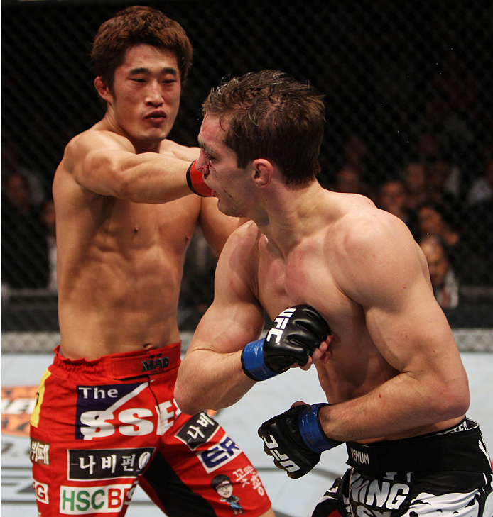 MACAU - MARCH 01:  (L to R) Dong Hyun Kim lands a punch on John Hathaway exchange punches in their welterweight fight during the UFC Fight Night event at the Venetian Macau on March 1, 2014 in Macau. (Photo by Mitch Viquez/Zuffa LLC/Zuffa LLC via Getty Images)