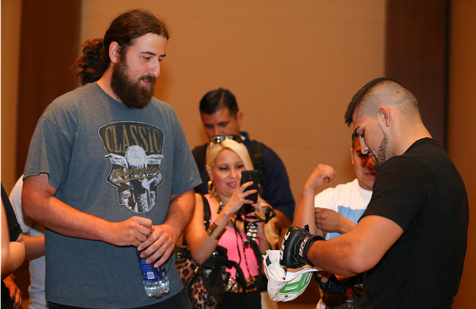 SAN ANTONIO, TX - JUNE 26:  Kelvin Gastelum signs autographs for fans after his open training session at the Grand Hyatt San Antonio on June 26, 2014 in San Antonio, Texas. (Photo by Ed Mulholland/Zuffa LLC/Zuffa LLC via Getty Images)