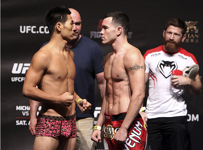 MACAU - AUGUST 22:  (L and R) Wang Anying and Colby Covington during the UFC weigh-in event at the Venetian Macau on August 22, 2014 in Macau, Macau.. (Photo by Mitch Viquez/Zuffa LLC/Zuffa LLC via Getty Images)