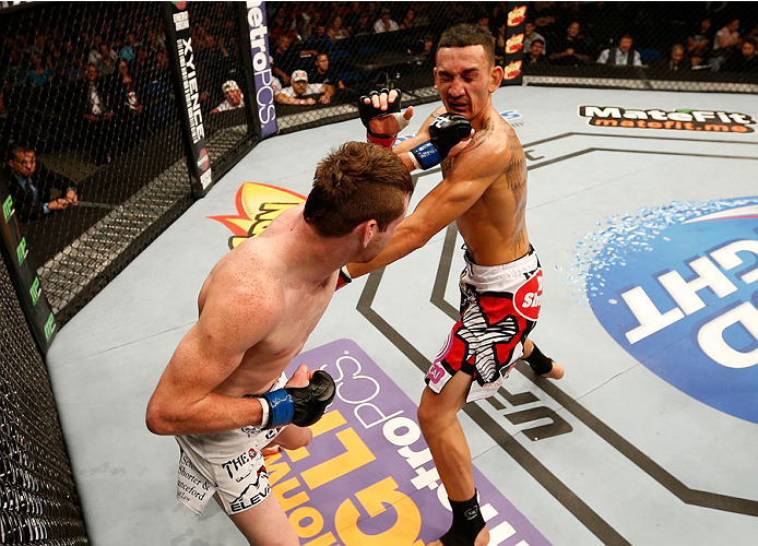 TULSA, OK - AUGUST 23:  (L-R) Clay Collard punches Max Holloway in their featherweight fight during the UFC Fight Night event at the BOK Center on August 23, 2014 in Tulsa, Oklahoma. (Photo by Josh Hedges/Zuffa LLC/Zuffa LLC via Getty Images)