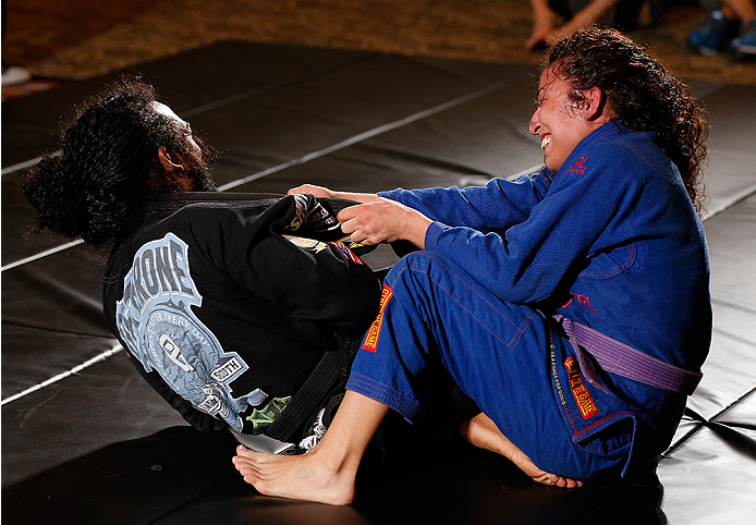 TULSA, OK - AUGUST 21: (L-R) Benson Henderson grapples with his wife Maria during a UFC open training session for media and fans at the Hyatt Regency Hotel on August 21, 2014 in Tulsa, Oklahoma. (Photo by Josh Hedges/Zuffa LLC/Zuffa LLC via Getty Images)