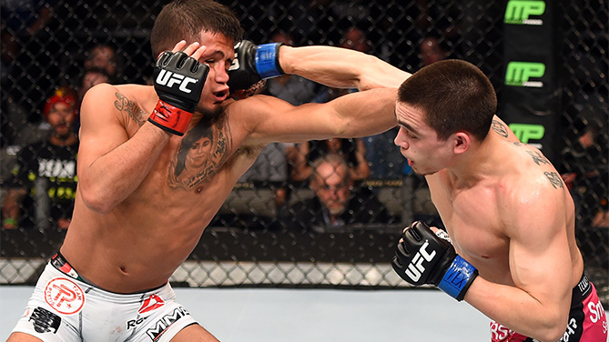 (R-L) Ryan Benoit lands a punch to the face of Sergio Pettis in their flyweight bout during the UFC 185 event at the American Airlines Center on March 14, 2015 in Dallas, Texas. (Photo by Josh Hedges/Zuffa LLC)