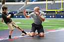ARLINGTON, TX - AUGUST 02:  UFC fighter Georges St-Pierre works out with eight year-old, Christian Rivera during a UFC World Tour open workout ahead of a UFC Welterweight Title fight at the AT&T Stadium on August 2, 2013 in Arlington, Texas.  Georges St-Pierre and Johny Hendricks will fight on November 16 in Las Vegas, Nevada.  (Photo by Ronald Martinez/Zuffa LLC/Zuffa LLC via Getty Images)