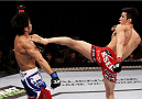 SINGAPORE - JANUARY 04: Kang Kyung Ho goes for a kick on Shunichi Shimizu in their bantamweight bout during the UFC Fight Night event at the Marina Bay Sands Resort on January 4, 2014 in Singapore. (Photo by Mitch Viquez/Zuffa LLC/Zuffa LLC via Getty Images)