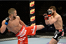 DULUTH, GA - JANUARY 15:  (L-R) Louis Smolka kicks Alpetkin Ozkilic in their featherweight fight during the UFC Fight Night event inside The Arena at Gwinnett Center on January 15, 2014 in Duluth, Georgia. (Photo by Jeff Bottari/Zuffa LLC/Zuffa LLC via Getty Images)