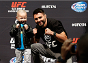 VANCOUVER, BC - JUNE 13:  Carlos Condit poses for photos with young fans after a Q&A session before the UFC 174 weigh-in at Rogers Arena on June 13, 2014 in Vancouver, Canada.  (Photo by Josh Hedges/Zuffa LLC/Zuffa LLC via Getty Images)