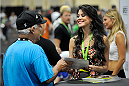 LAS VEGAS, NV - JULY 5:  UFC Octagon Girl Camila Rodrigues de Oliveira gins an autograph for a fan during the UFC Fan Expo at the Mandalay Bay Convention Center on July 5, 2014 in Las Vegas, Nevada. (Photo by Todd Lussier/Zuffa LLC/Zuffa LLC via Getty Images) *** Local Caption ***Camila Rodrigues de Oliveira