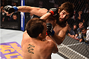 PHOENIX, AZ - DECEMBER 13:  (L-R) Joe Ellenberger punches Bryan Barberena in their lightweight fight during the UFC Fight Night event at the U.S. Airways Center on December 13, 2014 in Phoenix, Arizona.  (Photo by Josh Hedges/Zuffa LLC/Zuffa LLC via Getty Images)