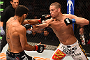 PHOENIX, AZ - DECEMBER 13:  (R-L) Nate Diaz punches Rafael dos Anjos of Brazil in their lightweight fight during the UFC Fight Night event at the U.S. Airways Center on December 13, 2014 in Phoenix, Arizona.  (Photo by Josh Hedges/Zuffa LLC/Zuffa LLC via Getty Images)