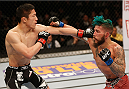 LAS VEGAS, NV - JANUARY 03:  (L-R) Kyoji Horiguchi punches Louis Gaudinot in their flyweight bout during the UFC 182 event on at the MGM Grand Garden Arena January 3, 2015 in Las Vegas, Nevada.  (Photo by Josh Hedges/Zuffa LLC/Zuffa LLC via Getty Images)