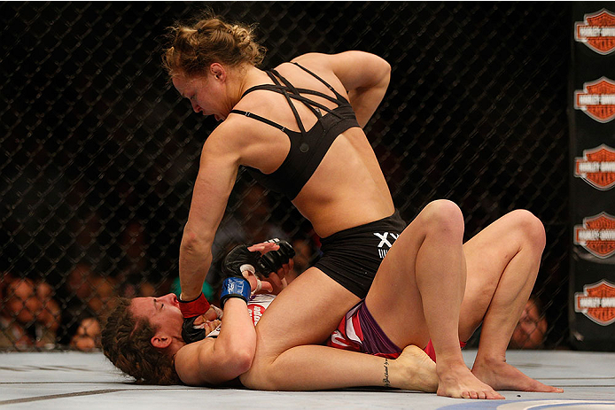 LAS VEGAS, NV - DECEMBER 28:  Ronda Rousey (top) punches Miesha Tate in their UFC women's bantamweight championship bout during the UFC 168 event at the MGM Grand Garden Arena on December 28, 2013 in Las Vegas, Nevada. (Photo by Josh Hedges/Zuffa LLC/Zuffa LLC via Getty Images) *** Local Caption *** Ronda Rousey; Miesha Tate